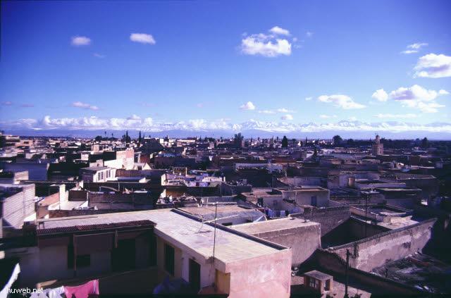 af13_blick_vom_restaurant_auf_den_djemaa__el-fna-platz_(gaukler,_schlangenbeschwoerer,_wahrsager)_hintergrund_atlas_gebirge_marokko_27.12.85-5.1.86,_marrakech.jpg