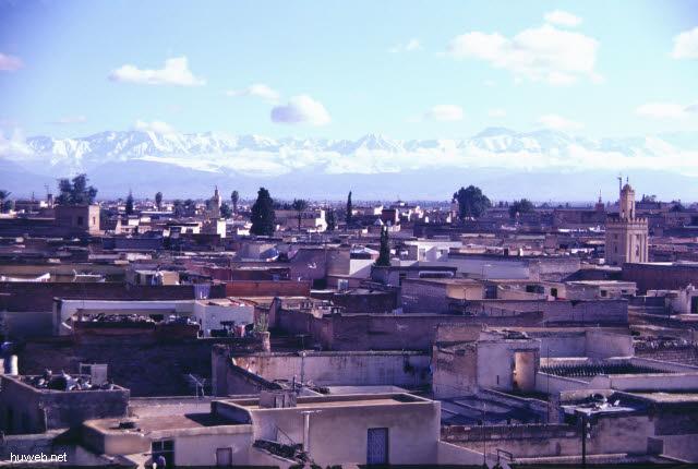 af14_blick_vom_restaurant_auf_den_djemaa__el-fna-platz_(gaukler,_schlangenbeschwoerer,_wahrsager)_hintergrund_atlas_gebirge_marokko_27.12.85-5.1.86,_marrakech.jpg