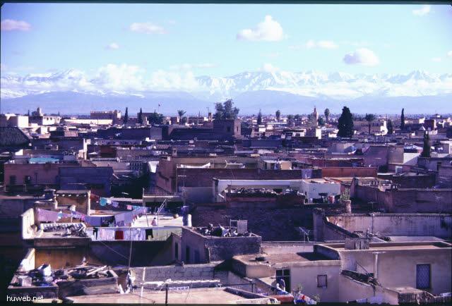 af15_blick_vom_restaurant_auf_den_djemaa__el-fna-platz_(gaukler,_schlangenbeschwoerer,_wahrsager)_hintergrund_atlas_gebirge_marokko_27.12.85-5.1.86,_marrakech.jpg